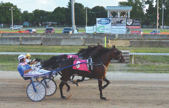 "In the closest finish of the night, Hugh ""Sandy"" Beatty leads Parklane Cupid (6) across the finish line just barely ahead of runner-up My Cam Girl (1) and third-place Dragonfly, in the seventh race, Aug. 1 at the Greene County Fair in Xenia."