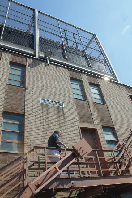 Greene County Sheriff Gene Fischer climbs the jail fire escape following an inmate escape in 2018.