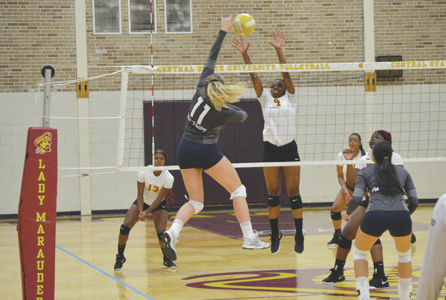 Central State freshman hitter Diamond Lester (4) goes up to contest a shot by Ohio Valley's Jessica Rafay (11), during Monday night's women's college volleyball match in Wilberforce.