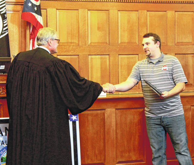 Anna Bolton | Greene County News Judge Stephen Wolaver shakes the hand of Jon Holmes, the fifth graduate of Greene County Veterans' Court Sept. 27. Holmes, of Fairborn, spent four years of Navy service aboard the USS Abraham Lincoln, a Nimitz class aircraft carrier, and 18 months in the specialty court program.