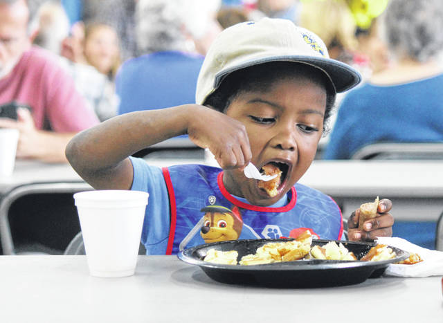 Anna Bolton | Greene County News Josh Hutchison takes a bite of pancakes at the Cedarville Township Fire Department pancake breakfast Aug. 31 to kick off CedarFest, a Labor Day weekend celebration.