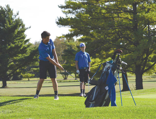 Xenia's Kyle Lane chips onto the Twin Base Golf Club hole no. 4 as teammate Wyatt Cowdrey looks on, during Thursday's boys high school varsity golf match in Fairborn.