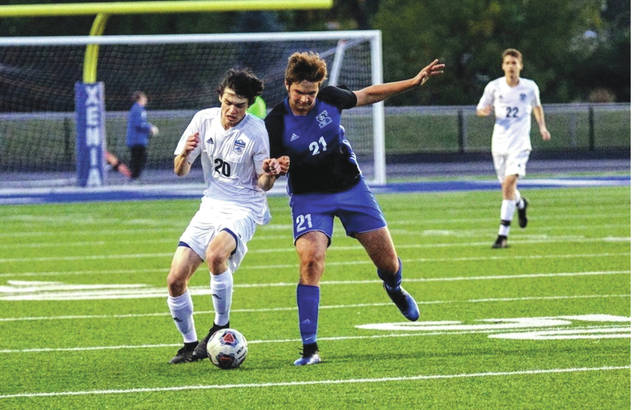 Fairborn senior midfielder Cayden Campbell (20) battles Xenia junior midfielder Ian Cushman (21) for control of the ball, during Tuesday's Division I boys soccer first round match at Doug Adams Stadium in Xenia.