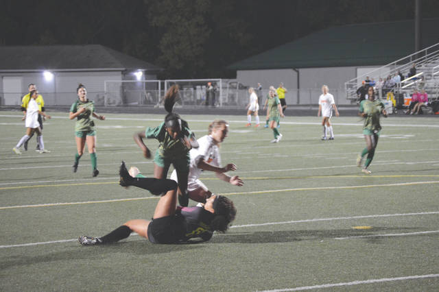 Northmont goalie Taylor Pritchett (00) crashes into Beavercreek's Kaileigh Nuessgen (18), and sends a Thunderbolt defender flying over her, in the first half of Wednesday's girls varsity soccer match in Clayton.