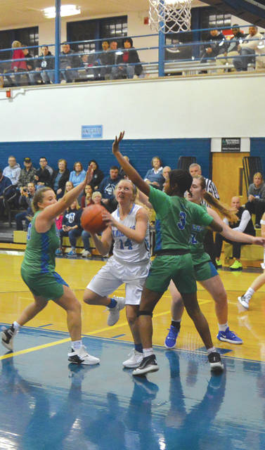 Margaret Kensinger (14) of Legacy Christian puts up a shot while surrounded by a trio of Chaminade Julienne Eagles, Tuesday Nov. 26 in Xenia.