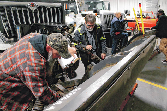 Anna Bolton | Greene County News District 8 auto technicians and mechanics, including Craig Haddix and Tom Bargo, inspect a snow plow Oct. 6 in the new ODOT Greene County garage.
