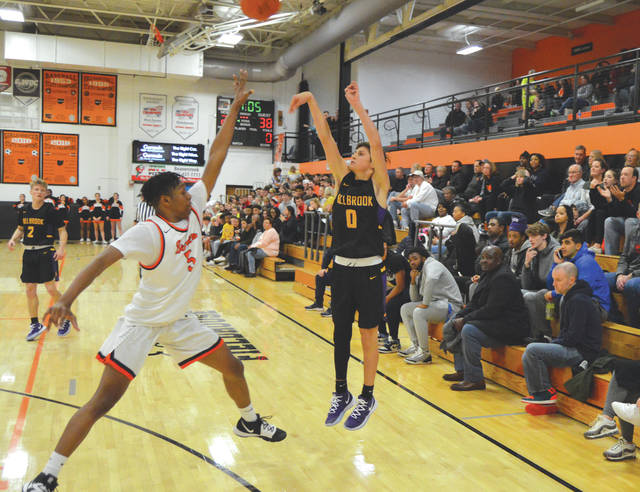 Sophomore Ryan Chew (0) gets off a three-point shot before Beavercreek's Siloam Baldwin (5) can close in, during the second half of Tuesday's boys high school basketball game at Beavercreek High School. Chew led all scorers with 21 points.