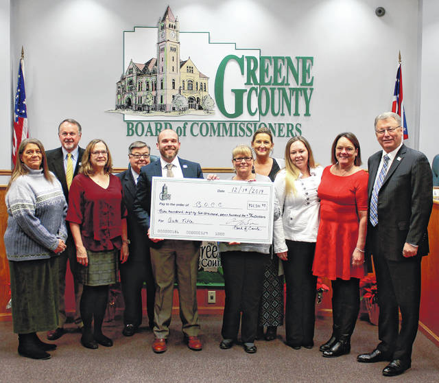 Anna Bolton | Greene County News Greene County commissioners Dick Gould, Bob Glaser and Tom Koogler accept an auto title fund check from Greene County Clerk of Courts A.J. Williams (center) and Auto Title Division staff members (left to right) Cathy Miller, Theresa Lehmenkuler, Missy Lamb, Lisa Connolly, Stacy Donovan and Gina Horsley.