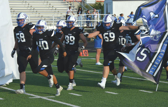 Bookends from the very beginning, Xenia High School seniors Gavin Gerhardt (58, far left) and E.J. Wilson (69, far right) charge through the school banner as they take the field for the start of the 2019 high school football season. The two Bucs signed college National Letters of Intent on Wednesday, Dec. 18.