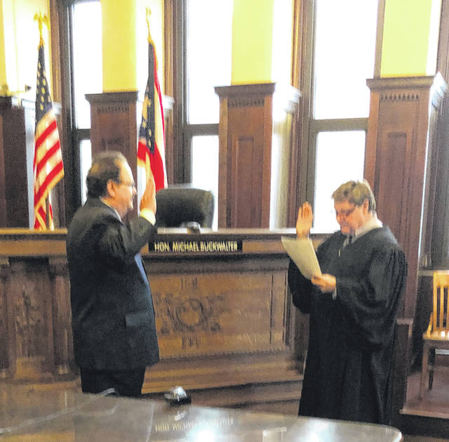 Submitted photo Chris Chrystal is sworn in as the new Greene County Veteran's Service commissioner by Judge Michael A. Buckwalter at the Greene County courthouse. Chrystal was appointed by Buckwalter and Judge Stephen A. Wolaver to serve a five year term and will represent the American Legion Post 526 in Fairborn. A United States Marine Corps veteran, Chrystal served 14 years in the Greene County Veteran' Services Office and recently retired after serving as executive director.