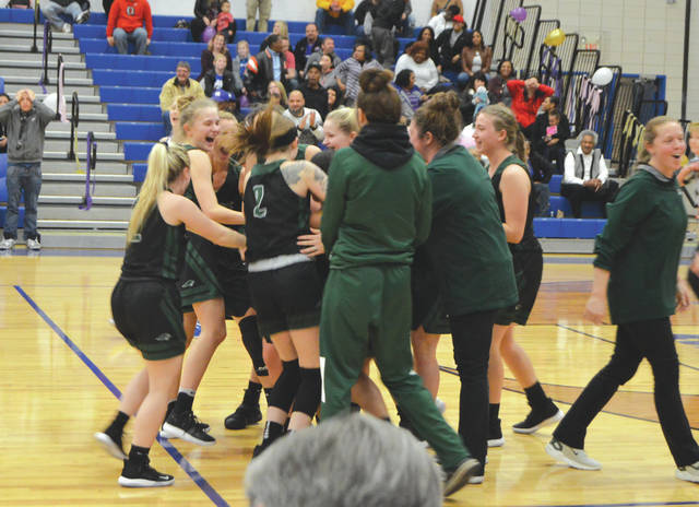 Greenville senior Morgan Gilbert is mobbed by her Green Wave teammates after hitting a buzzer beating 3-pointer to win Wednesday night's girls varsity basketball game against host Xenia.