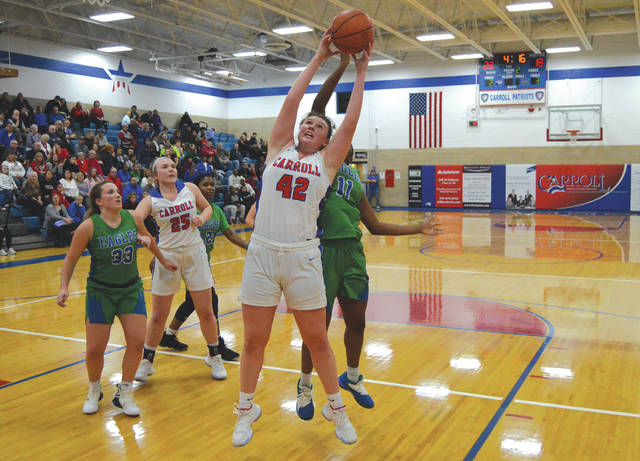 Carroll's Julia Keller snags an offensive rebound during the first half of Wednesday's girls high school basketball game against visiting Dayton Chaminade Julienne.