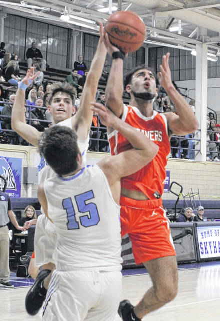 Beavercreek's Yousef Saleh takes a shot while Fairborn's Brody Munger defends. Saleh finished with a triple double.