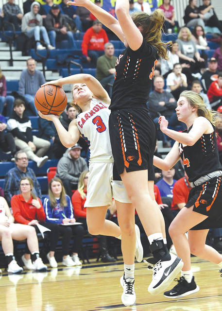Carroll's Sarah Ochs (3) works to shoot over Anna Landing of Beavercreek, during Saturday's girls high school varsity basketball game at the Flying To The Hoop basketball showcase in Kettering.