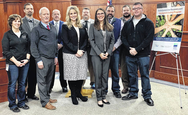 Submitted photo BWC added Greene County and two others to a worker recovery program. Pictured are Lori Dodge-Dorsey, director of Madison County Job & Family Services; Patrick Closser, mayor of London; Madison County Commissioner Mark Forrest; London Police Chief Glenn Nichol; Stephanie McCloud, administrator/CEO of the Ohio Bureau of Workers' Compensation; Madison County Commissioner David Hunter; Greta Mayer, CEO of Mental Health & Recovery Board of Clark, Greene & Madison Counties; Madison County Commissioner Dr. Tony Xenikis; Madison County Administrator Rob Slane; and Eric Mata, person in recovery.