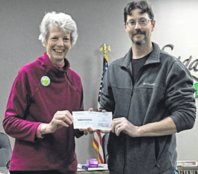 Submitted photo Hope Taft, founder of Little Miami River Kleeners, receives a donation from John Rammel, co-owner of TrailHeadz Hammock and Accessories, LLC.
