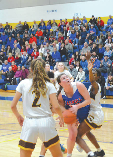 Carroll High School senior Julia Keller, shown here weaving through Roger Bacon defenders in last week's regional title game in Springfield, was named to the Division II All-Ohio second team on Wednesday.