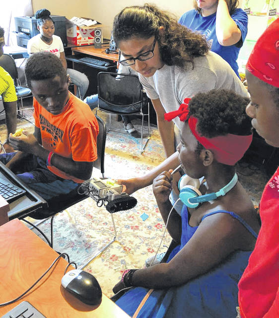 Submitted photos Beavercreek Girl Scout Neeti Prasad introduces Kids In New Directions (KIND) students to robotics.