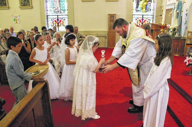 Anna Bolton | Greene County News A First Communion class carries gifts to Fr. Andrew Cordonnier during mass at St. Paul Catholic Church in Yellow Springs in May 2019. During the coronavirus pandemic, local churches like St. Paul are broadcasting services on Facebook Live and YouTube instead of meeting in person.