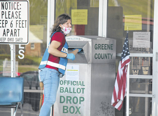 Photos by Anna Bolton | Greene County News A Greene County Board of Elections worker places a voted ballot in the drop box outside the office at Ledbetter Road April 28, the last day of the extended vote-by-mail primary.