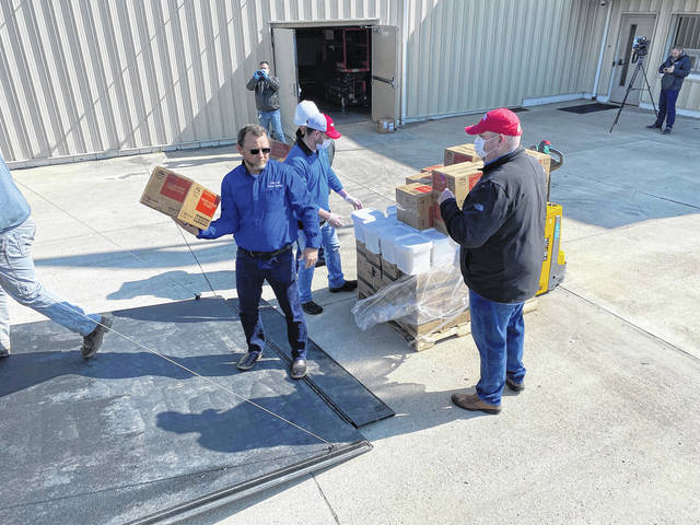 Incoming Rotary President Matt Bennett (right) helps load items into a trailer.