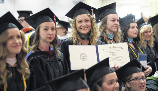 Submitted photos Graduates from a recent Cedarville University commencement ceremony show off a diploma during the ceremony.