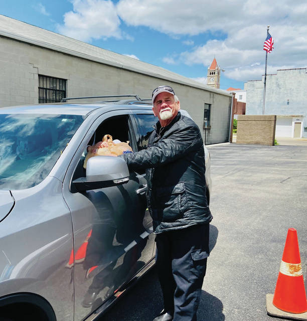 Photo courtesy Xenia Elks Xenia Elks Lodge Exalted Ruler Ron Woods hands a hot meal to a community member in the drive-through.