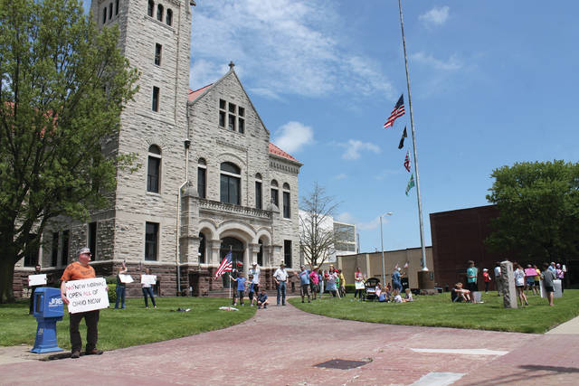 "Photos by Anna Bolton | Greene County News A ""Free Ohio Now"" group rallied on the Greene County Courthouse lawn May 16. About 40 protesters — half adults and half teens and children — held up American flags and ""Open Ohio"" and ""Facts Over Fear"" signs. They waved as cars drove by, some honking."