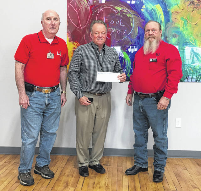 Submitted photo Xenia Lions Club members David Jordan (left) and Rodger Sanders (right) present a check to Toward Independence CEO Mark Schlater.