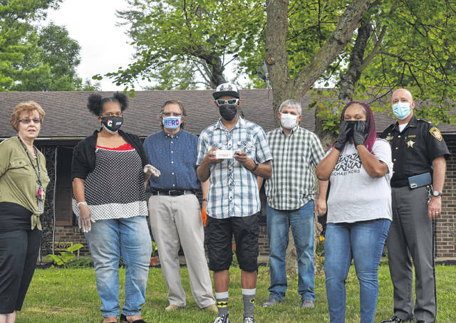 Submitted photo Dee Yoakum, Javon and Karron's mother; Felicia Chappelle, a friend; Jonathan Platt, Story Chain executive director; Javon Yoakum, Story Chain MP3 player recipient; Josh Carson, Greene County Board of Developmental Disabilities behavior support specialist; Mary Evans, Story Chain audio editor and program manager; and Maj. Kirk Keller, Greene County Sheriff's Office, attend the MP3 player delivery to Javon July 16 in Beavercreek. Story Chain originated as a program in jails helping incarcerated parents read to their children; it has since expanded to reach the developmental disabilities community.