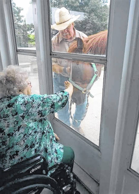 Submitted photos A Greenewood Manor resident reaches out to pet a horse through the glass June 26. The horse is led by Tim Spradlin, director of Finally Home Farm, a non-profit providing equine therapy.