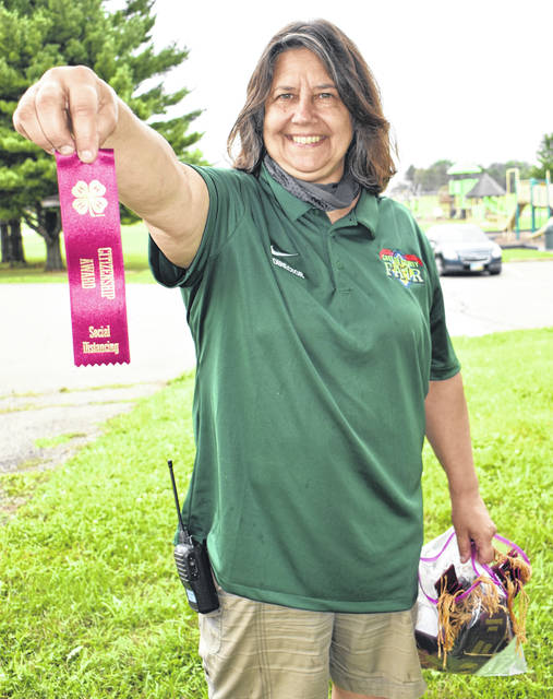 Submitted photo Greene County fair board members are distributing burgundy social distancing ribbons to junior fair participants who are practicing social distancing and other COVID-19 safety precautions at the fair this week. Pictured, Pat Zehring, Greene County Agricultural Society member, accepts the ribbons on the first day of the fair. The ribbons are courtesy of Central State University and its 4-H program.