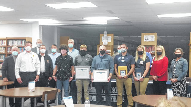 The Fairborn School Board, Fairborn Fire Chief Dave Reichert, and Mayor Paul Keller present Coach Bronson Marlett, trainers Jaci Combs and TJ Tillman, and students Bailey Snapp and Andrew Yeary with awards Oct. 1 for saving an athlete's life.