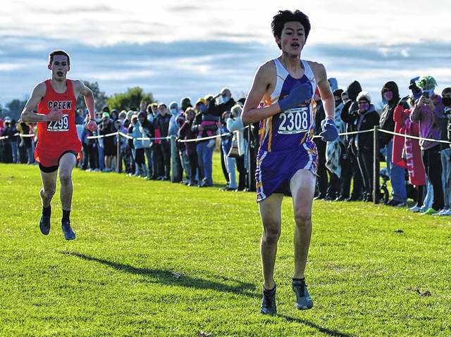Photos by Chris Greene | Greene County News Bellbrook's Takumi Ford is on his way to a Division-I district cross country championship. Beavercreek's Connor Ewert finished second, a little more than a second behind.
