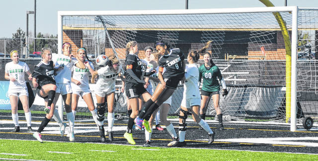 Scott Halasz | Greene County News Beavercreek's Ashley Vaughn (left), Maggie Holstein (center), and Cassie Rodriguez (right) try to make a play on the ball after a corner kick against Mason in a Division-I district final Saturday. Mason's Elizabeth Berry heads the ball away before the Beavers have a chance to score.