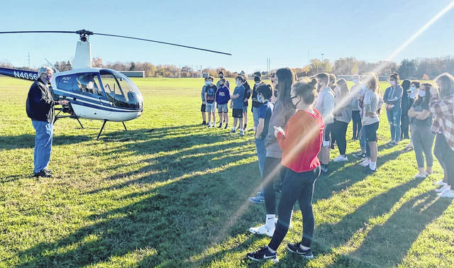 Submitted photos Students in Jennifer St. Pierre's eighth grade flight class at Bellbrook Middle School had a close-up look at a helicopter Monday thanks to local pilot Finley Barfield, who flew his R22 helicopter to the school.