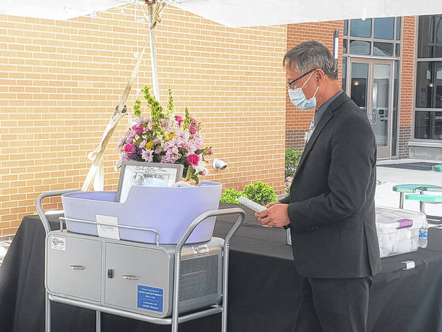 A chaplain prays over the cradle in memory of all babies that have passed away.