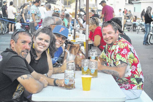 Todd Diener, Jennifer Crall, Shawn Crall, and Jim Guyton toast Jennifer Crall's birthday outside Devil Wind Brewery during Xenia's Oktoberfest.