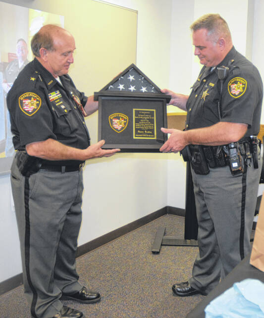 Photos by Karen Rase | Greene County News Sheriff Gene Fischer presents a flag and plaque to long-time Deputy Shawn Bradley.