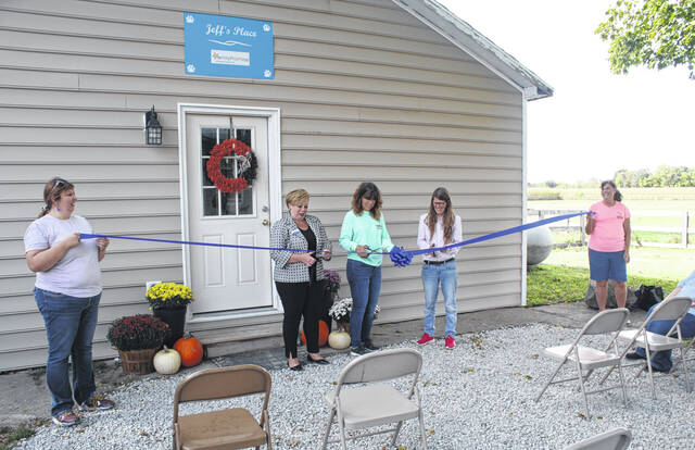 Submitted photos Cutting the ribbon on Jeff's Place are Xenia Mayor Sarah Mays, Regina Willen, founder and executive director of HALO K9 Behavior Consultation, and Stephanie Hines, Family Promise of Greene County board member and wife of the late Jeff Hines (Jeff's Place).