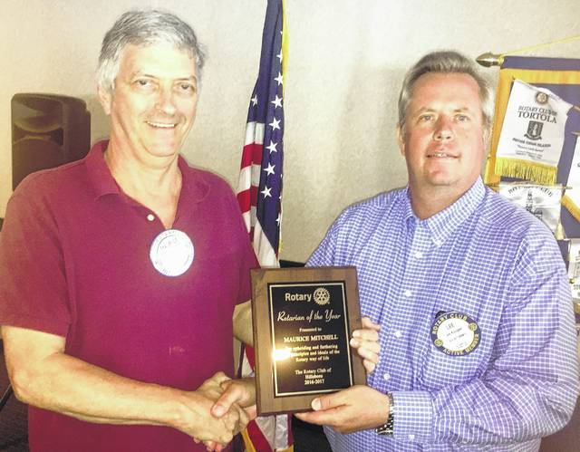 Maurice Mitchell, above left, was named Rotarian of the Year this week by the Hillsboro Rotary Club. Mitchell serves as the club's cashier and works the check-in table each week, as well as handling other duties that help keep the club functioning smoothly. He is shown receiving his award from Rotary president Lee Koogler. Below, Koogler, left, is presented with a plaque in recognition of his service as Rotary president, which concluded this week. Koogler was presented the award by incoming Rotary president Reid Sharp.