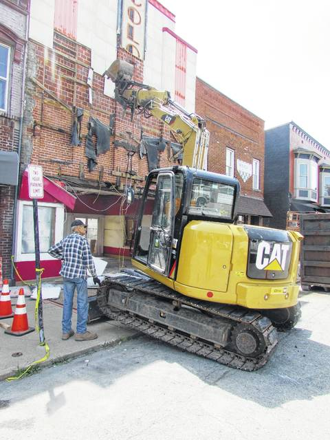 Workers begin tearing down the front of the Colony Theatre in Hillsboro on Monday after it was determined that the structure was too unstable to save following demolition of the rear of the building.