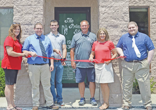 Highland County Chamber of Commerce Executive Director Melissa Elmore and Robyn Coomer, left, of the Classic Real Estate Co. are pictured with representatives of The Print Shop, which recently reopened for business on Northview Drive in Hillsboro.