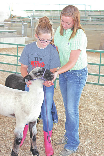 Sarah Young from the Fairfield FFA helps Allie Pavey from the Fab Five 4-H Club work on her showmanship skills.