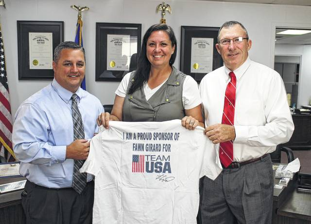 Highland County Board of Commissioners President Shane Wilkin, left, and commissioner Terry Britton, right, pause their meeting Wednesday for a photo with Fawn Girard, a local archer who is currently raising money to compete in the World Archery 3-D Championships. As reported by The Times-Gazette, Girard, an accomplished archer, is a member of the U.S. national 3-D archery team, and will compete in the championships Sept. 19-24 in Robion, France. Though she is a member of the team, Girard must raise her own money to make the trip to France possible. The U.S. team does not provide financial support to its members, not even for the uniforms in which they compete. A U.S. Archery Fund account through Fifth Third Bank can be used for those who can make donations. Also, donations can be made via Paypal transfer using Girard's email (fawngirard@aol.com) or by sending donations to Girard at 931 Gibson Road, Martinsville, Ohio 45146. Girard is also selling t-shirts for $20 each.