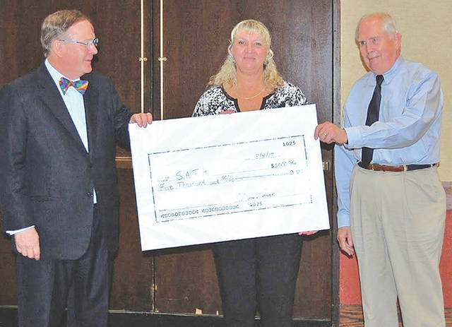 """On Aug. 4 at the Region 14 Administrator Conference, Linda Allen, director of SATH (Supplementary Assistance to the Handicapped), was presented a monetary donation of $5,000 from Dr. Douglas Reeves, founder of Creative Leadership Solutions. Reeves was the keynote address speaker for over 125 administrators from Adams, Brown, Clinton, Fayette and Highland counties. Reeves talked with the administrators about """"Leading through Uncertainty: From the Classroom to the Boardroom."""" Dr. William Larson, director of the Ohio University Leadership Project (OULP), shared in the celebration as OULP financially supported in securing Reeves for the event. Shown in the photo, from left, are Reeves, Allen and Larson."""