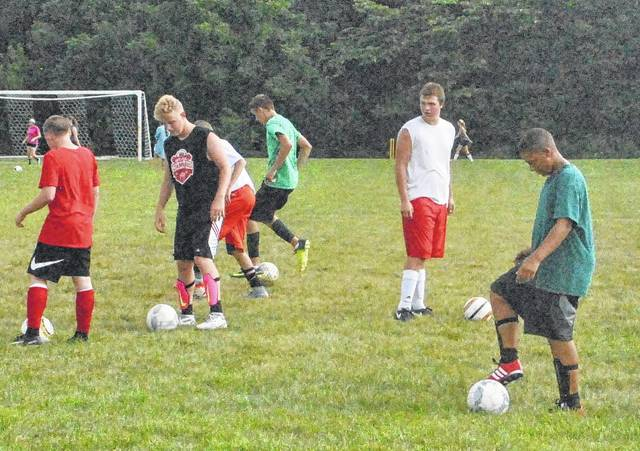 The Fairfield Lions soccer team warms up before practice begins.