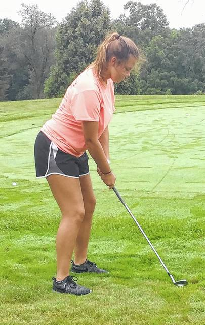A member of the Lady Mustangs golf team practices chipping from the edge of the practice green at White Oak Golf Course.