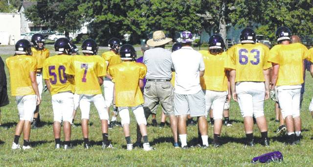 The McClain Tigers varsity football team circles up to take part in a drill during practice.