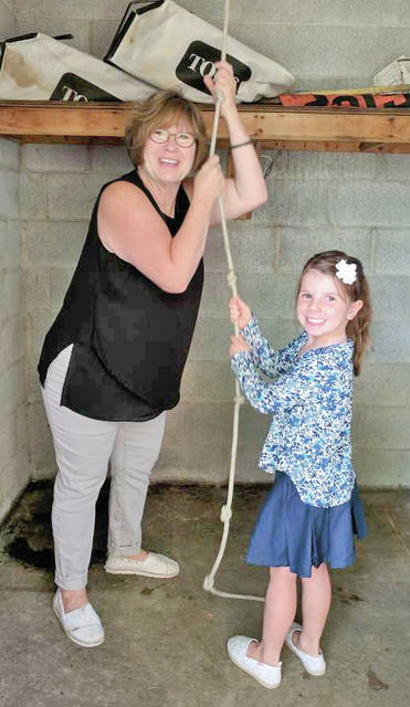 The kindergarten students at Greenfield Elementary rang the victory bell Tuesday to mark the beginning of their first school year. Kindergartners were assembled Tuesday morning the occasion. All three kindergarten classes had a chance to pull the rope and watch the bell swing back and forth in the tower. It was a great way to celebrate the first week of their formal education. For many years, the victory bell rang once every morning, calling children from all over the city to come to school. It has been used to celebrate athletic victories and it rings out at graduation time as well. At the end of the 2017-18 school year, the fourth grade students will continue this tradition by ringing the victory bell, signifying their last day in school as elementary students. In the photo, teacher Cathy Rivas and one of the kindergarten students are shown ringing in the new year.